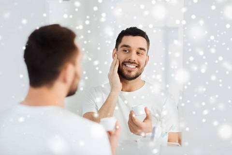 beauty, skin care, winter and people concept - smiling young man applying cream to face and looking to mirror at home bathroom over snow